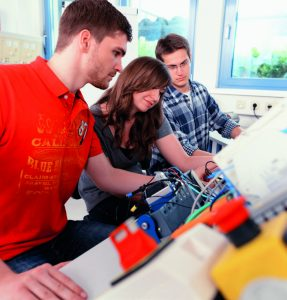 students working together in mechatronics laboratory of college, close up